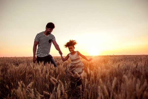 Father and daughter are running and jumping through a field of wheat during the golden hour of sunset