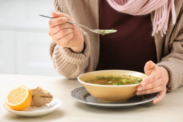 woman wearing a sweater and scarf cropped from the chest down eating soup at a table