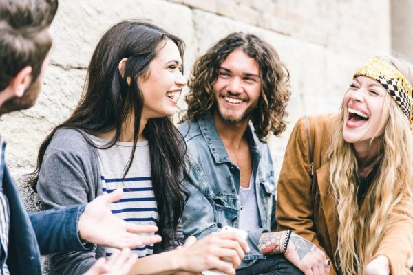 group of four young adults laughing and sitting against a wall