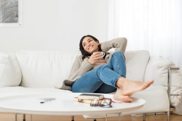 woman sitting on a couch with her feet on the coffee table smiling and holding a mug