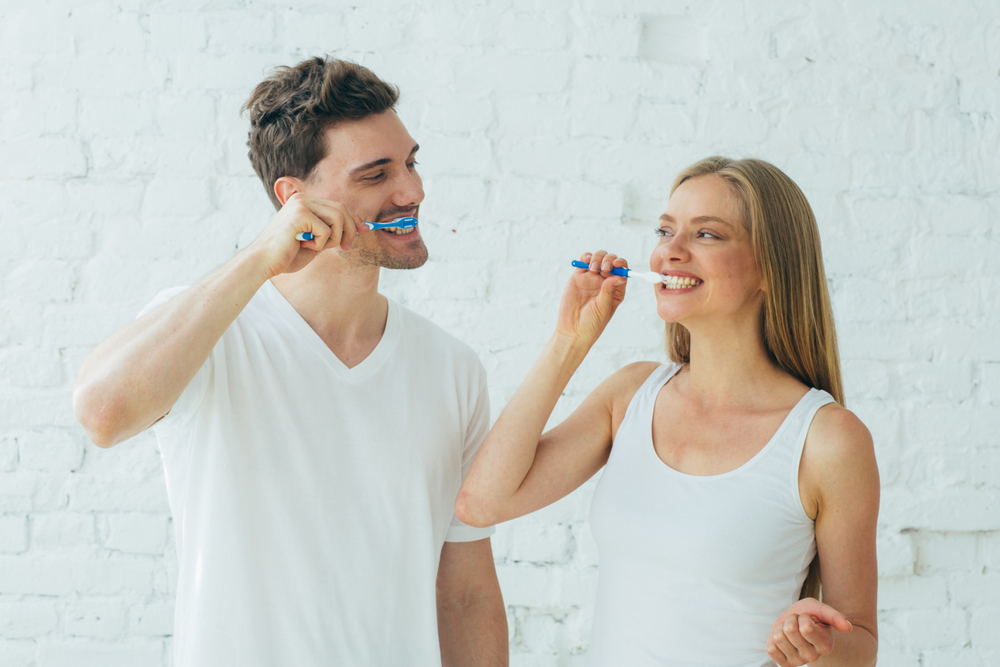 man and woman wearing white shirts standing in front of a white wall brushing their teeth and smiling at each other